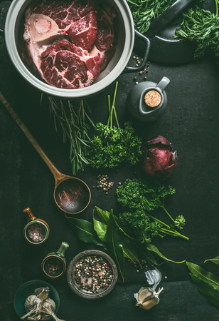 Raw meat with bone in cooking pot on dark kitchen table background with herbs and spices for broth, meat bone stock or soup, top view