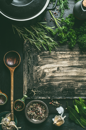 Food background with cooking pan, wooden spoon fresh seasoning and spices on dark rustic background, top view Imagens