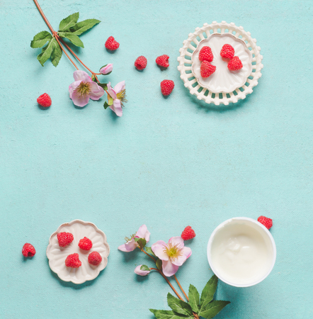 Raspberries and yogurt cup on pastel blue table background, top view. Frame. Copy space. Healthy summer food