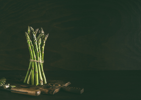 Green asparagus bunch standing on dark rustic kitchen table background with wooden cutting board and knife. Copy space