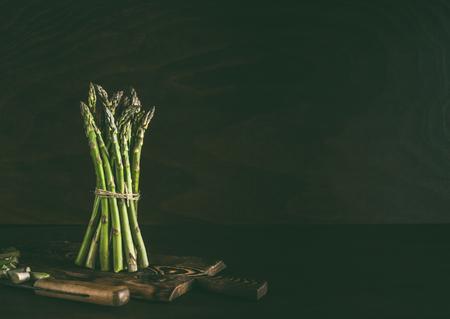 Groene asperges bos staande op donkere rustieke keukentafel achtergrond met houten snijplank en mes. Ruimte kopiëren Stockfoto