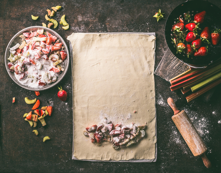 Sheet of dough with diced rhubarb and strawberries ingredients for strudel pie, on rustic kitchen table, top view. Seasonal baking. Organic food. Step by step Zdjęcie Seryjne