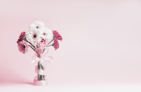 Beautiful gerbera flowers bunch with ribbon standing on pastel pink background. Copy space