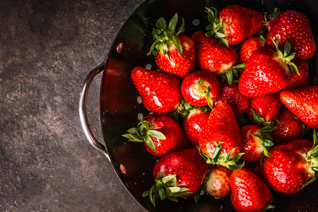 Close up of fresh strawberries in black colander bowl, top view