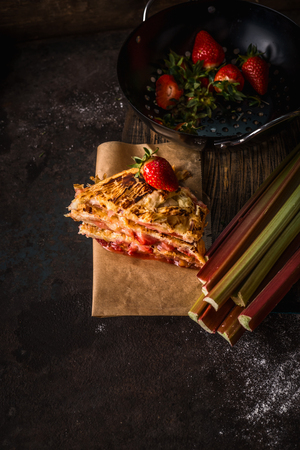 Pieces of rhubarb strawberries cake on dark kitchen table . Seasonal pastries