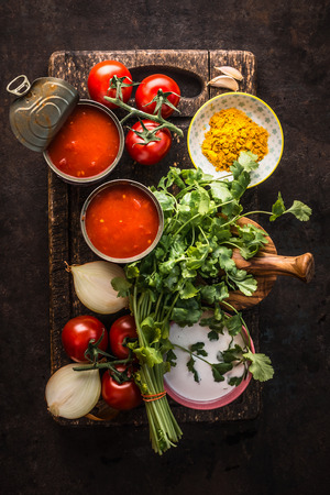 Healthy fresh ingredients for tomato soup on dark rustic kitchen table background, top view