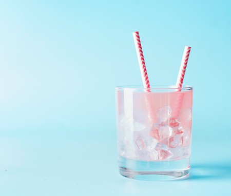 Pink iced refreshment drink in glass with paper drink straw on blue background. Copy space. Summer pastel pink cocktail.