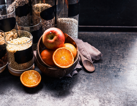 Healthy vegan breakfast ingredients. Nuts and cereals in glasses for granola and fruits in coconut bowl on dark rustic kitchen table. Copy space. Healthy lifestyle