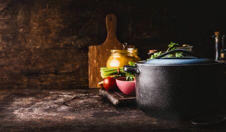 Olla de hierro fundido con hierbas frescas, especias y utensilios de cocina para cocinar sabrosa en mesa rústica. Alimentación saludable. Cocina casera. Oscuro. Naturaleza muerta. Fondo de alimentos. Copia espacio Foto de archivo