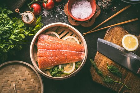 Salmon fillet and lemon slices in bamboo steamer on dark rustic kitchen table with ingredients and tools. Healthy eating and cooking. Asian cuisine Zdjęcie Seryjne