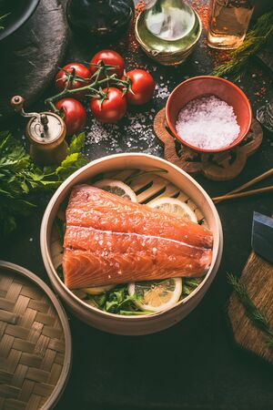 Raw salmon fillet in bamboo steamer on dark rustic kitchen table with fresh ingredients and tools. Healthy eating and cooking. Dieting concept. Asian cuisine. Cooking preparation Stockfoto