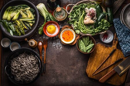 Asian food background. Tasty vegetarian ingredients. Various green vegetables,  soba noodles - buckwheat noodles, flavor salt and chili hot sauce on rustic kitchen table background with chopsticks