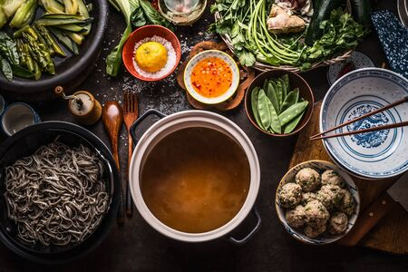 Various asian food ingredients for tasty soba noodles soup around cooking pot with delicious miso broth or stock on rustic kitchen table background, top view. Asian cuisine background. Healthy eating Stock Photo - 125147332