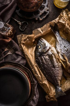 Roasted dorado fishes on backing sheet on dark rustic  table background with tableware and kitchen utensils, top view. Seafood concept. Healthy eating