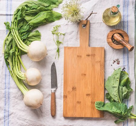 Raw young turnip with greens on light kitchen table with empty cutting board and knife, top view. Healthy vegetarian eating and cooking concept. Copyspace