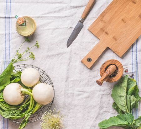 Food background with raw young turnip  with greens on light kitchen table with cutting board and knife, top view. Healthy vegetarian eating and cooking concept. Copy space for your design Stock Photo