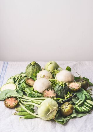 Heap of various green organic seasonal farm vegetables  for tasty vegetarian cooking on light kitchen table. Rustic style. Healthy eating and cooking concept. Clean food
