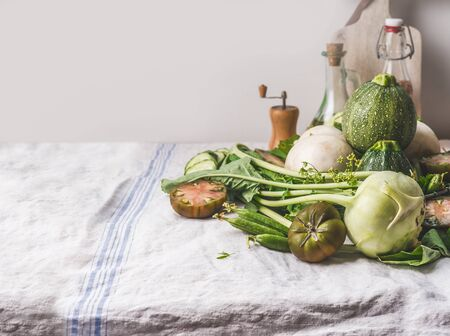 Various green organic seasonal vegetables  for tasty vegetarian cooking lie on light kitchen table. Rustic style. Healthy eating and cooking concept. Clean food
