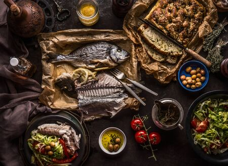 Baked dorado fish on dark table with salad bowl , focaccia bread, tomatoes and olives, top view.  Mediterranean lunch or dinner. Italian food concept Фото со стока