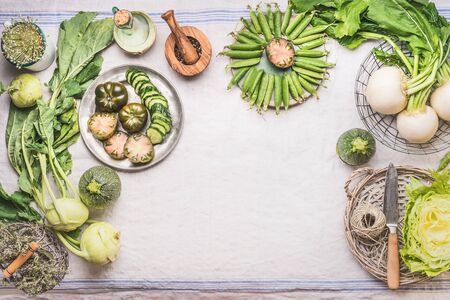 Food background with green vegetables in bowls on light table with knife: green peas, kohlrabi, lettuce, zucchini, cucumber, green tomatoes. Top view. Clean vegetarian eating and cooking concept.