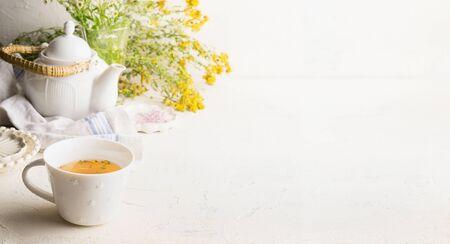 Kräuterteehintergrund mit Tasse mit gelbem Tee, Teekanne und frischen Kräutern und Blumen auf weißem Tisch an der Wand. Bio-Tusan-Tee. Konzept der wilden Heilpflanze. Kopieren Sie Platz für Ihr Design oder Produkt.