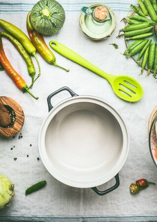 Empty cooking pot with spoon and fresh vegetables in light kitchen table background, top view.  Copy space. Healthy food eating concept. Copy space. Keto or paleo diet