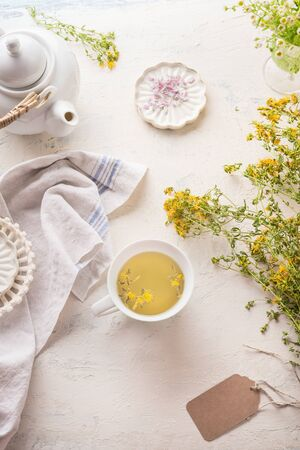 White cup of yellow herbal tea on light table with tea pot and fresh herbs and flowers. Organic Tutsan tea. Wild medicinal plant concept. Copy space for your design or product.