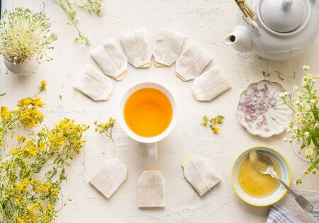 White cup with frame of tea bags with mock up of herbal tea on white table background, top view. Herbal tea setting with teapot , honey and fresh medical herbs and flowers. Healthy beverages concept Stok Fotoğraf - 126018269