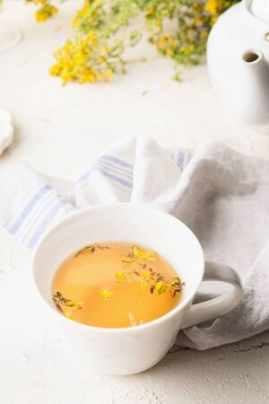 Close up of yellow herbal tea in white cup. Herbal medicine. Natural dietary supplement . Saint-Johns-wort tea