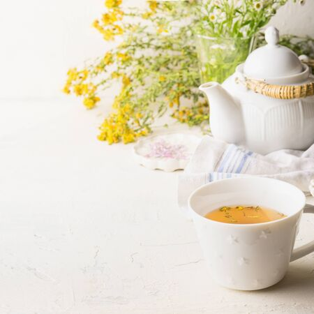 Cup of yellow herbal tea on white table background with teapot and fresh healing herbs and flowers. Herbal medicine. Natural dietary supplement Stok Fotoğraf
