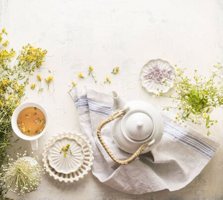 Herbal tea setting with fresh medical herbs , teapot and cup of tea. Saint-Johns-wort herbs and flowers on white table background, top view. Herbal medicine. Natural dietary supplement Stok Fotoğraf