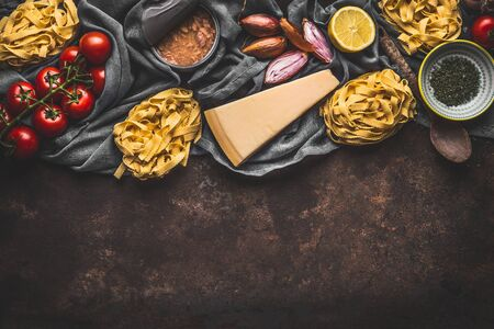Italian food ingredients for pasta with tuna tomatoes sauce, top view. Copy space. Pasta,parmesan, open tuna can, tomatoes, onion, lemon on dark rustic background. Stock Photo