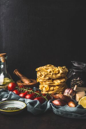 Homemade italian pasta with cooking ingredients on dark rustic kitchen table at wall background. Copy space. Italian cuisine. Still life