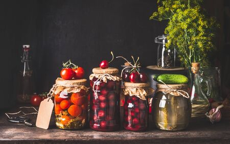 Preserved and fermented food in glass jars - pickles, jam, compote with tomatoes, cucumber and cherries on dark rustic background. Fermented food. Autumn canning. Conservation of farm harvest