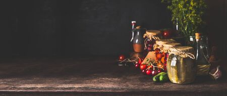 Food background with variety of preserved fermented vegetables and fruits from garden in glass jars on dark rustic background. Autumn canning. Conservation of harvest. Healthy homemade food. Banner Banco de Imagens