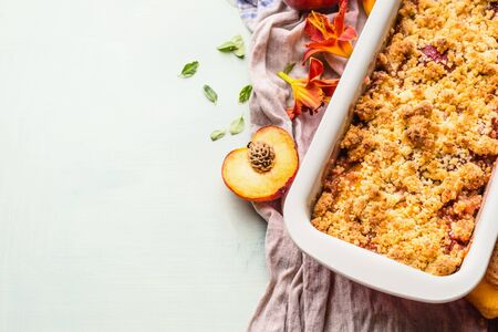 Yummy peach crumble dessert in baking pan on light