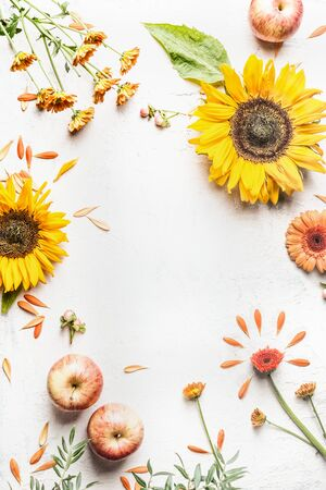 Late summer or autumn background with sunflowers, apples and other garden flowers on white desk. Top view. Flat lay. Frame. Seasonal layout. Floral composing.