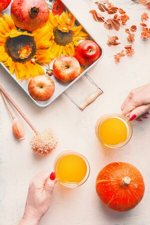 Glass mugs with hot yellow drinks: mulled wine or cider on white table background with sunflowers, pumpkin and autumn leaves, top view. Fall season enjoy. Copy space Flat lay. Imagens