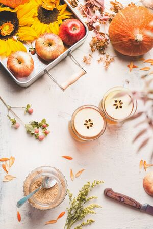 Autumn layout. Glass mugs with apple hot cider or apple mulled wine with apple slices on white desktop with sunflowers, pumpkin and autumn leaves, top view. Fall season enjoy. Copy space Flat lay.
