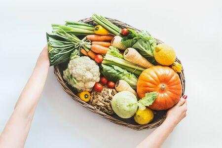 Vrouwelijke hand met dienblad met verschillende kleurrijke biologische groenten, groenten van de lokale markt op een witte bureauachtergrond. Gezonde voeding en schoon seizoensgebonden eetconcept. Bovenaanzicht. Schoon seizoens eten Stockfoto