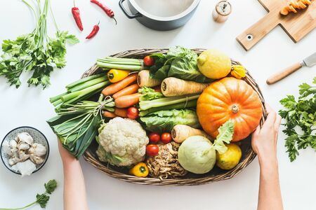 Female hands holding tray of various colorful organic farm vegetables on white table with pot, cutting board and knife. Healthy food and clean flat eating flat lay. Top view. Stock fotó