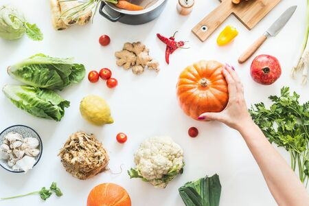Healthy food and clean seasonal eating concept. Various organic vegetables on white desk background with pot, cutting board and knife. Female hand holding pumpkin. Vegetarian background. Top view