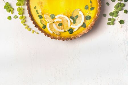 Food background with lemon tart topped with citrus slices and zest on white table background, top view. Copy space. Close up. Traditional french cuisine