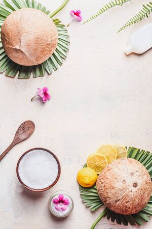 Coconut oil in wooden bowl with spoon and moisturizing cream on white desk background with tropical leaves and flowers , top view. Frame. Copy space. Flat lay. Modern skin care and cosmetic concept