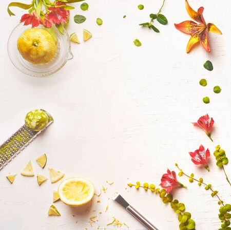 White food background with lemon juice, lime zest and flowers, top view Stock Photo