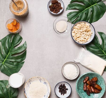 Vegan gluten-free cake ingredients: cashew , non dairy milk, almond flour, Coconut cream and milk, agar agar and dried fruits . Top view. Flat lay. Frame. Healthy food. Low-calorie Dieting.