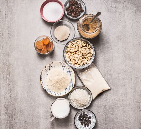 Healthy vegan gluten-free cake ingredients: cashew , almond flour, Coconut cream, non dairy milk, agar agar, Coconut butter, dried fruits on concrete background, top view. Plant based diet dessert