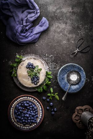 Top view of vegan no bake blueberry cake on dark rustic kitchen table background with fresh berries, side view. Healthy food