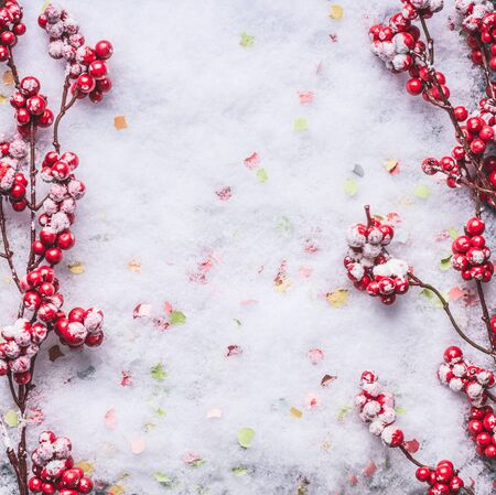 Red frozen berries on snow background. Winter and Christmas layout. Flat lay . Copy space