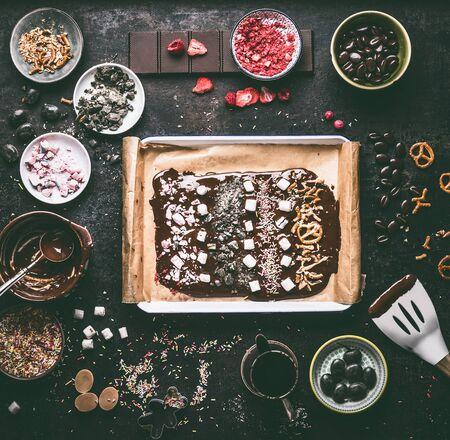 Preparation of homemade chocolate bark with various topping: melted chocolate in bowls , spatula, nuts, marshmallow, nuts, liquorice, caramel and candy on dark table. Top view. Copy space.